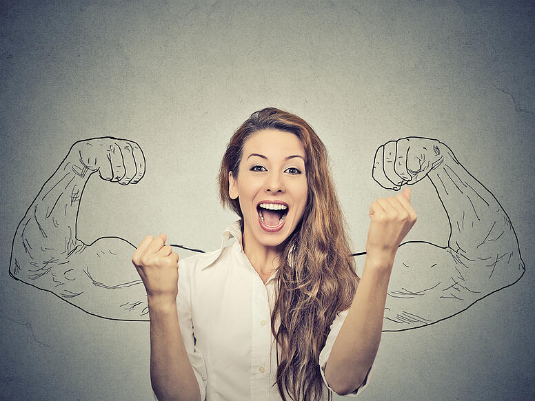 happy woman exults pumping fists ecstatic celebrates success on gray wall background